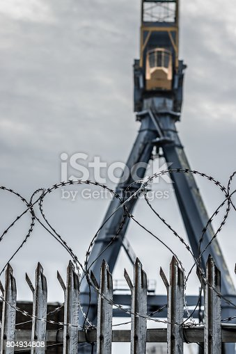 Crane, idle at a dry dock in Belfast Harbour (Northern Ireland), with metal fence and barbed wire in the foreground.