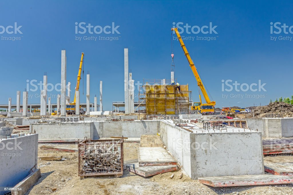 Crane is working with riggers, workers are assembly big mold for concreting stock photo