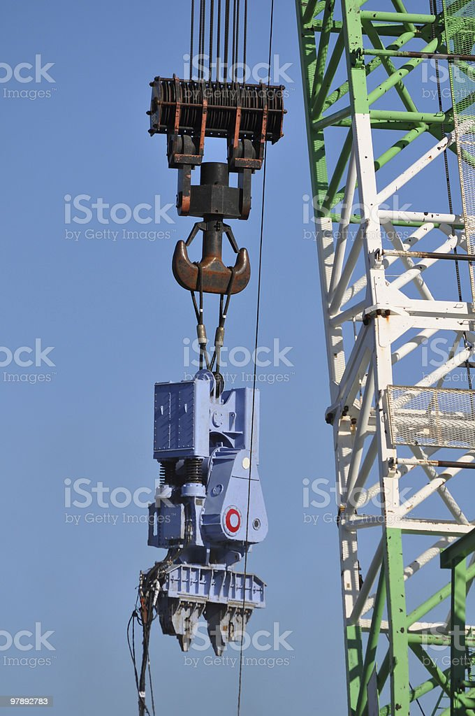 Crane lifting a heavy equipment royalty-free stock photo