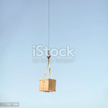 A construction crane and hook lifting a cardboard box.