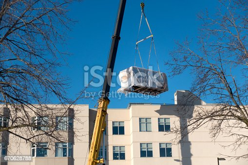 A large industrial crane lifts a heating, ventilation and air conditioning unit onto the roof of an apartment building.