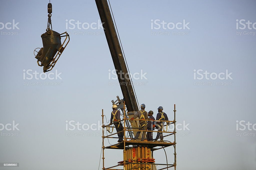 A crane lifting machineries while engineers are observing royalty-free stock photo
