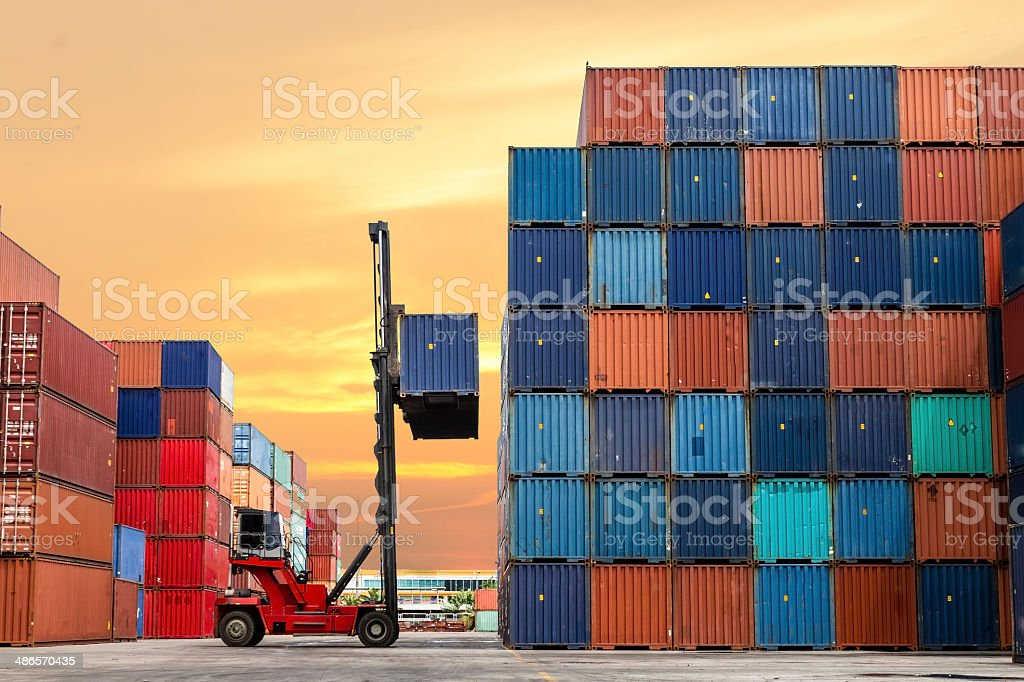 Crane lifting up container in yard Crane lifting up container in yard Activity Stock Photo