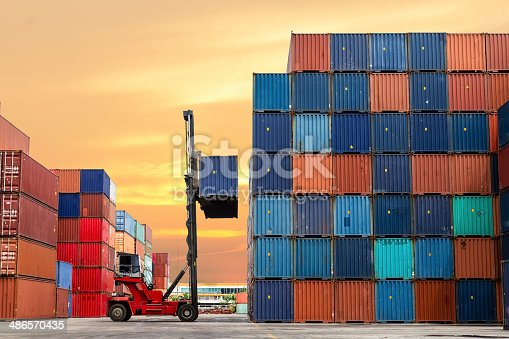 istock Crane lifting up container in yard 486570435