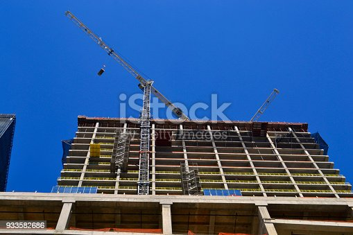 Crane lifts concrete flooring on a construction site in downtown Houston, Texas.