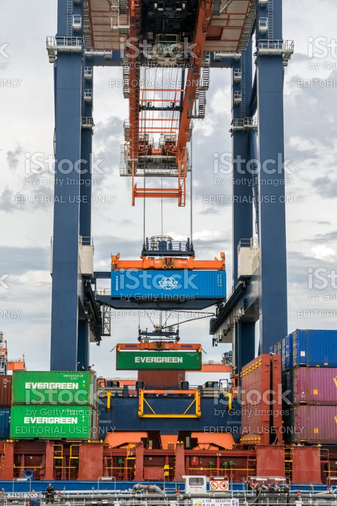 Crane loading a ship with a cargo container in the Port of Rotterdam stock photo