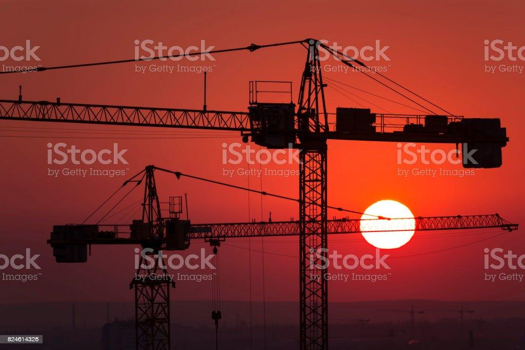 crane over the urban landscape sunset - stock image