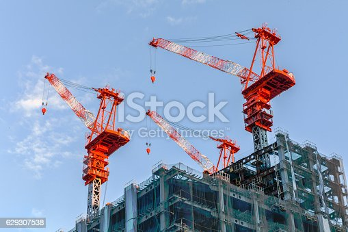 Cranes on top of a tall building.