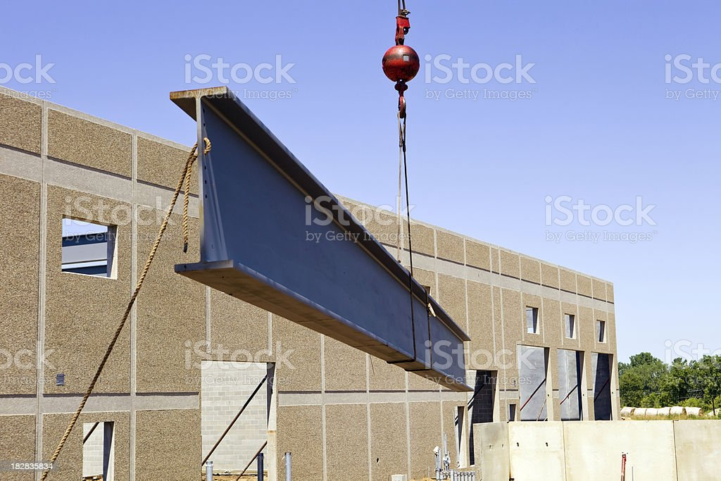 Crane raises a new Roof Beam at Commercial Construction Site royalty-free stock photo