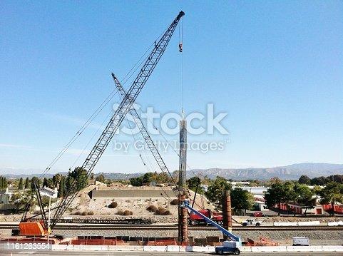 istock Crane Setting A Setting a Rebar Cage into a Column Form for the Future Bridge of Tustin Ranch Road in Tustin California 1161263554