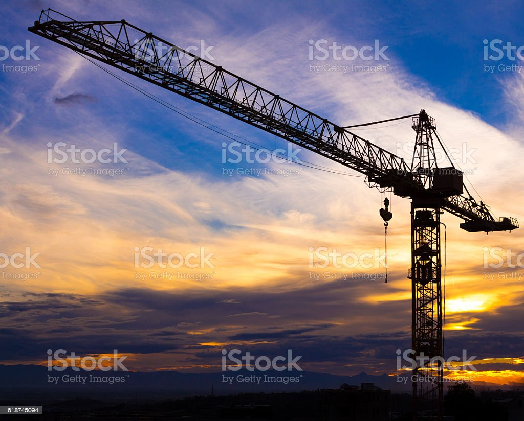 Crane silhouetted against the sunset with orange clouds stock photo