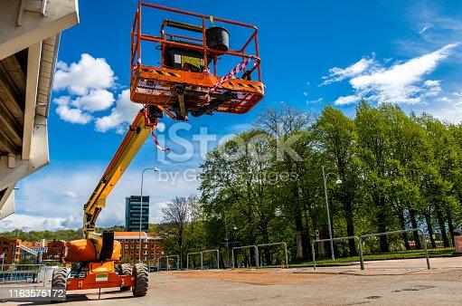 Telescopic crane boom against vibrant blue sky