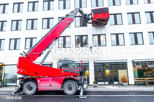 Telescopic crane boom with a container in a city enviroment