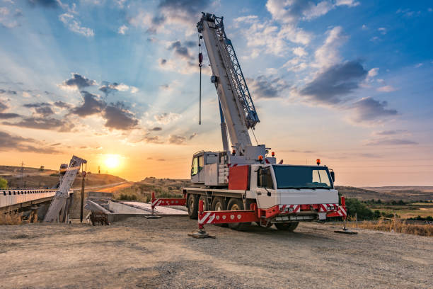 Crane trucks in the construction of a bridge Sunset building a highway bridge mobile crane stock pictures, royalty-free photos & images