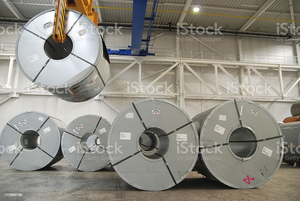 Crane with rolls of sheet steel stock photo