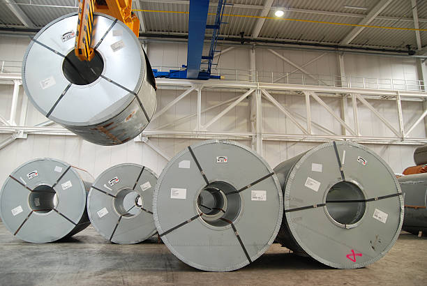 Crane with rolls of sheet steel stock photo