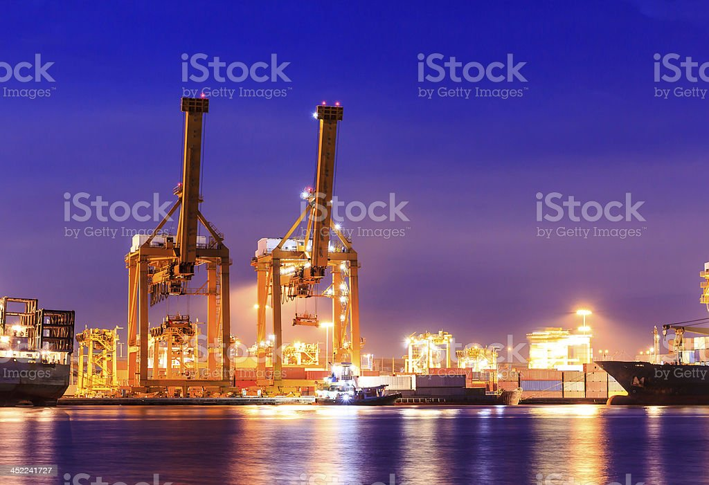 crane working with container cargo in shipyard at dusk royalty-free stock photo