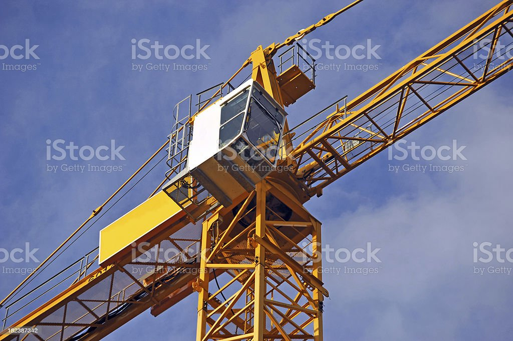 crane yellow diagonal before blue sky on construction site royalty-free stock photo