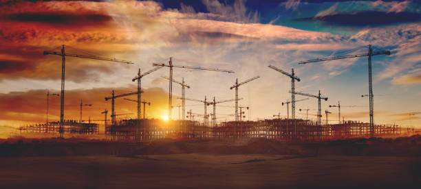 Cranes and building construction Construction and real estate industry. Sunset and foundation structure of houses. construction site stock pictures, royalty-free photos & images