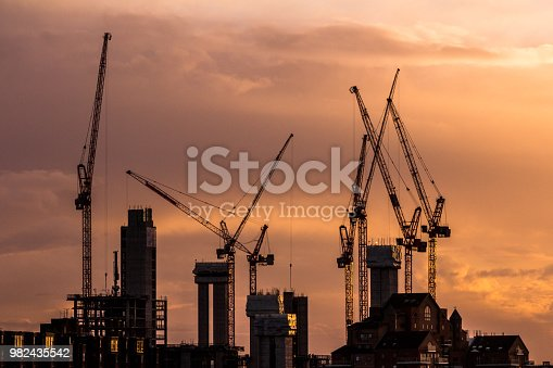 Color image depicting cranes and heavy duty construction equipment on the London skyline as the sun sets. The cranes have been busy constructing blocks of flats and apartments to ease the housing crisis in London and the south east of England. Lots of room for copy space.
