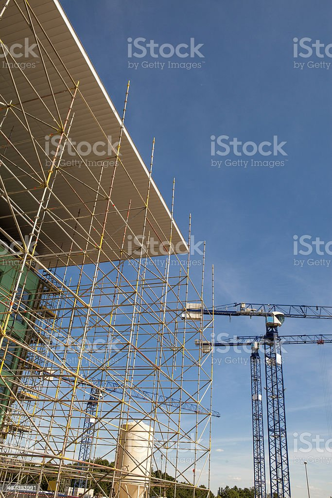 Cranes and scaffolding at  construction site royalty-free stock photo