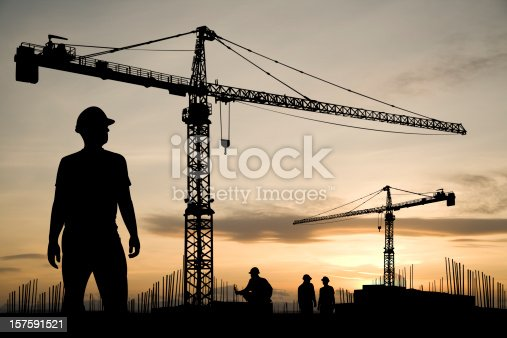 A construction worker stands ready to start a day of work as he looks out over a construction site. Off in the distance are two cranes.