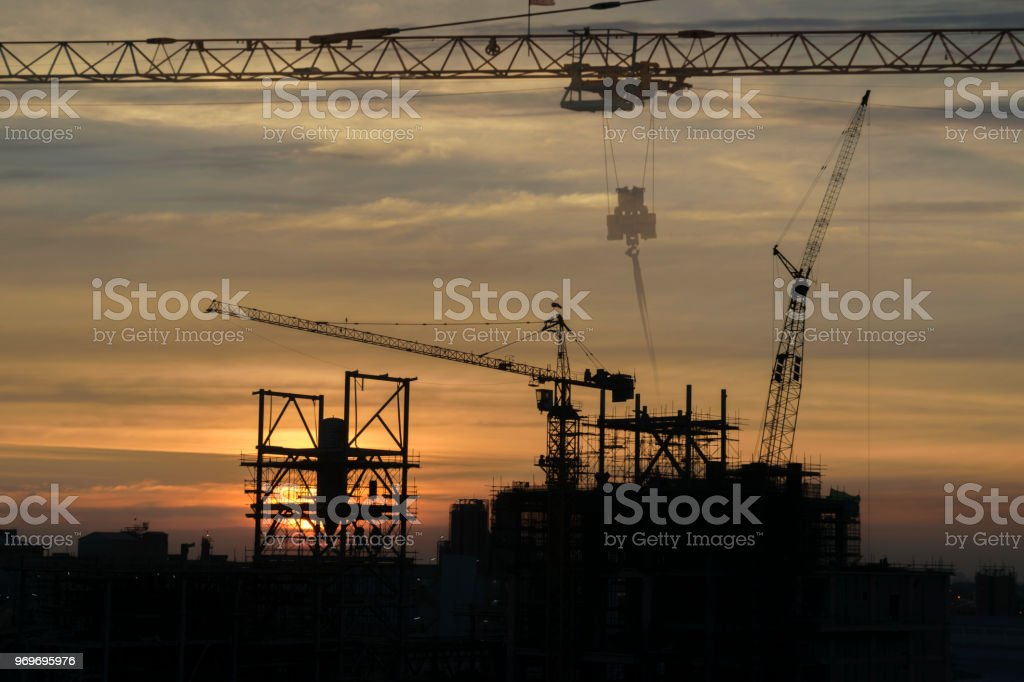 Tower cranes build large residential buildings at construction site...