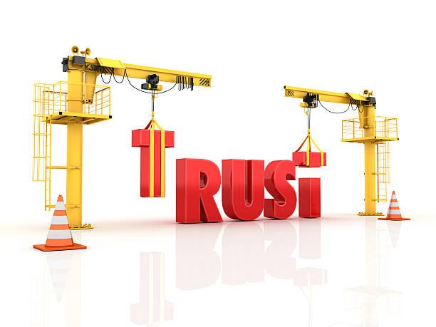 Cranes building the TRUST Word stock photo