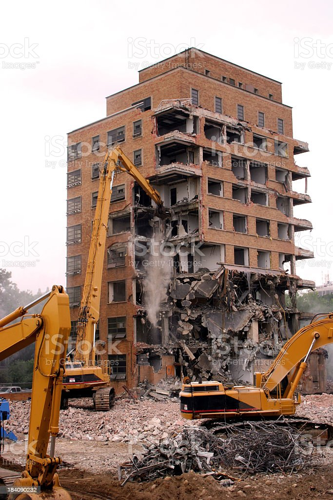 Cranes demolishing a brick building stock photo