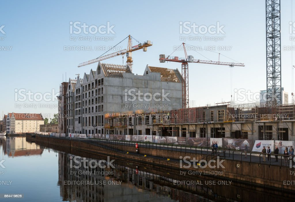 Cranes erecting new apartments near old town Gdansk stock photo