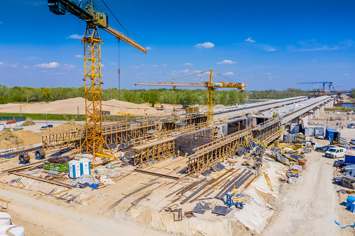 Cranes in the construction of a bridge for a highway. Aerial view