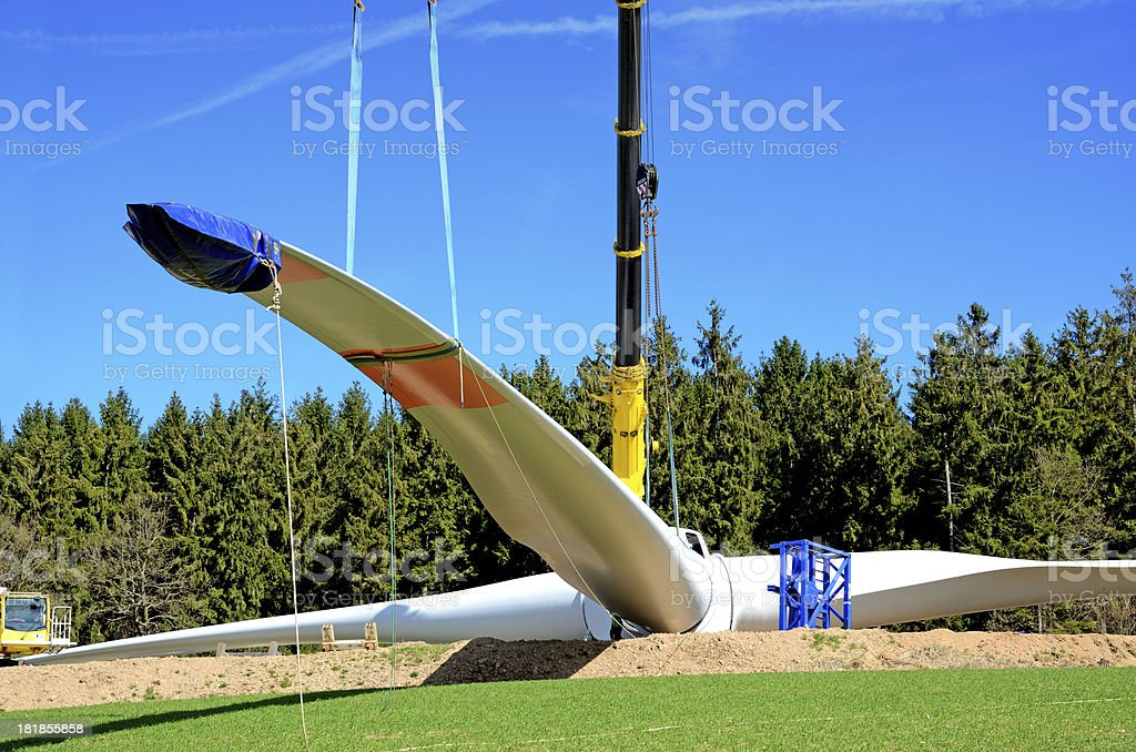 Cranes lift rotor blade on wind turbine construction site royalty-free stock photo