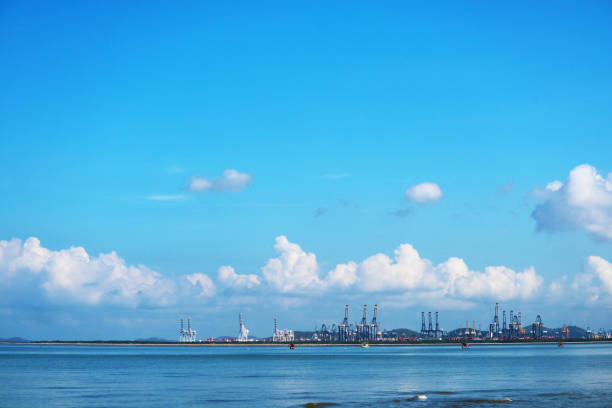 cranes on seaport and blue sky white tiny cloud and fishing boats stock photo