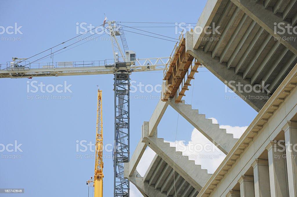 Cranes performing stadium construction royalty-free stock photo