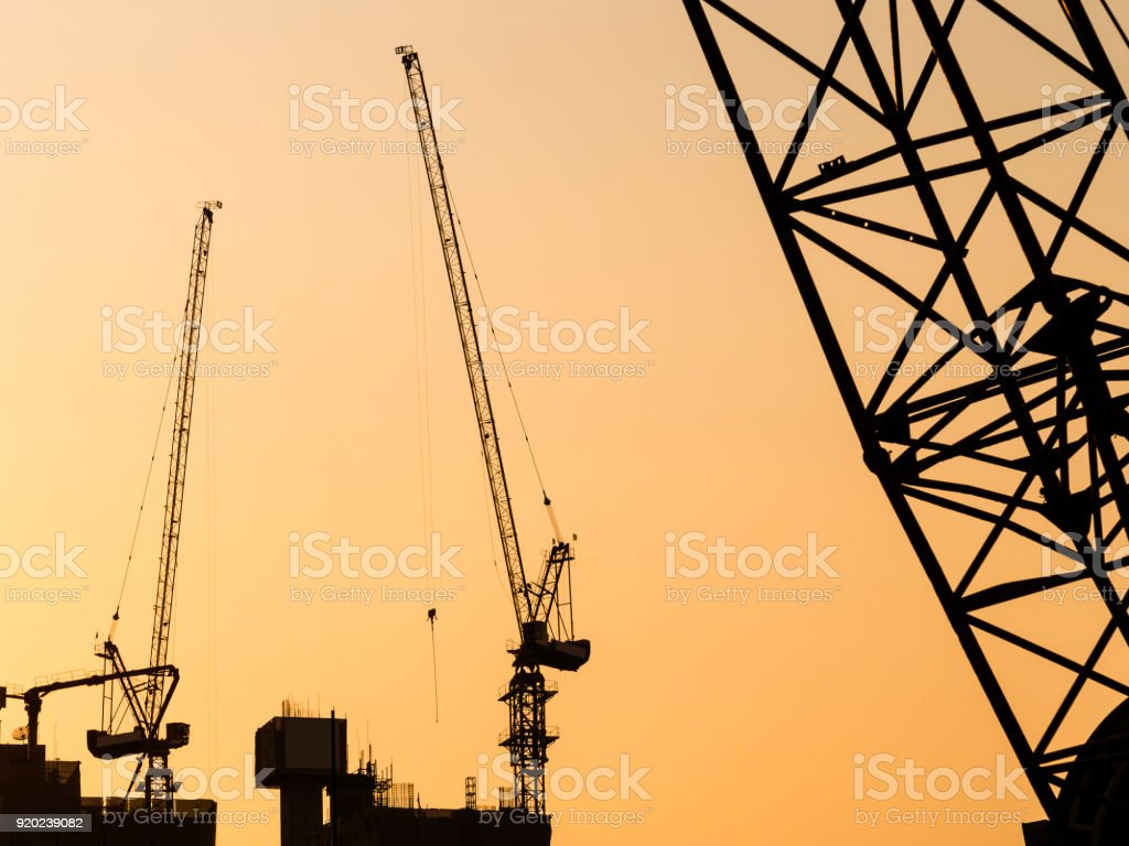 Cranes working on Building Construction site sunset sky Silhouette...