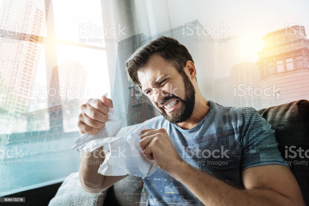 Crapping angry man sitting and tearing the document stock photo