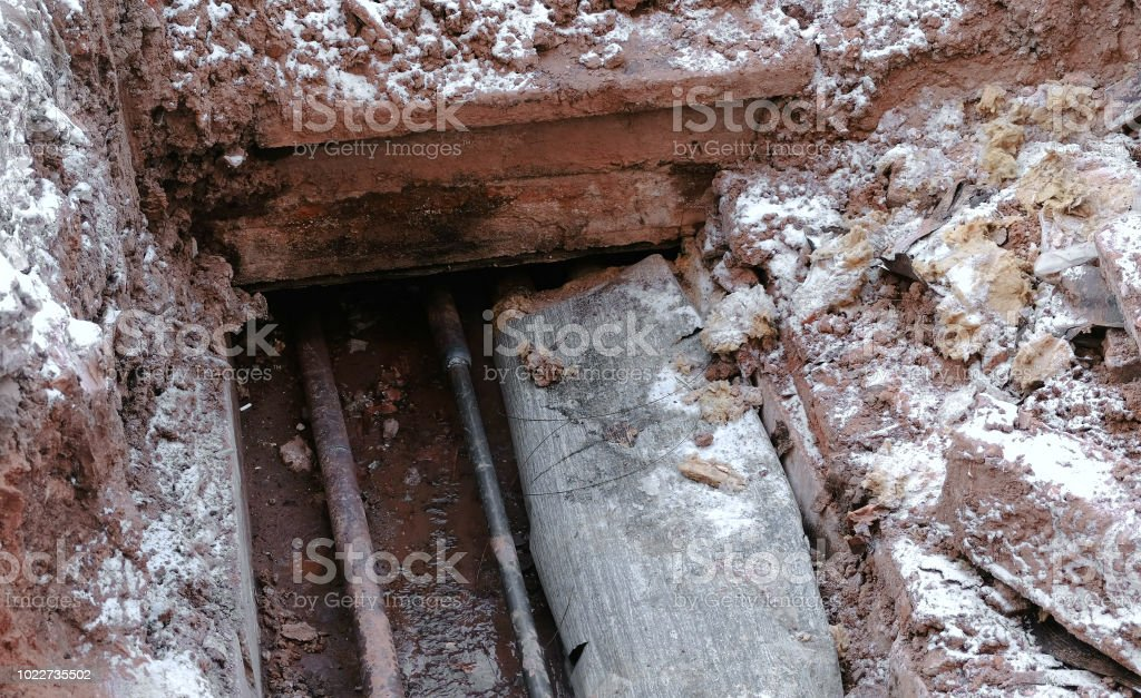 Crash, burst pipes and leaking water under the earth. Excavated pipes...