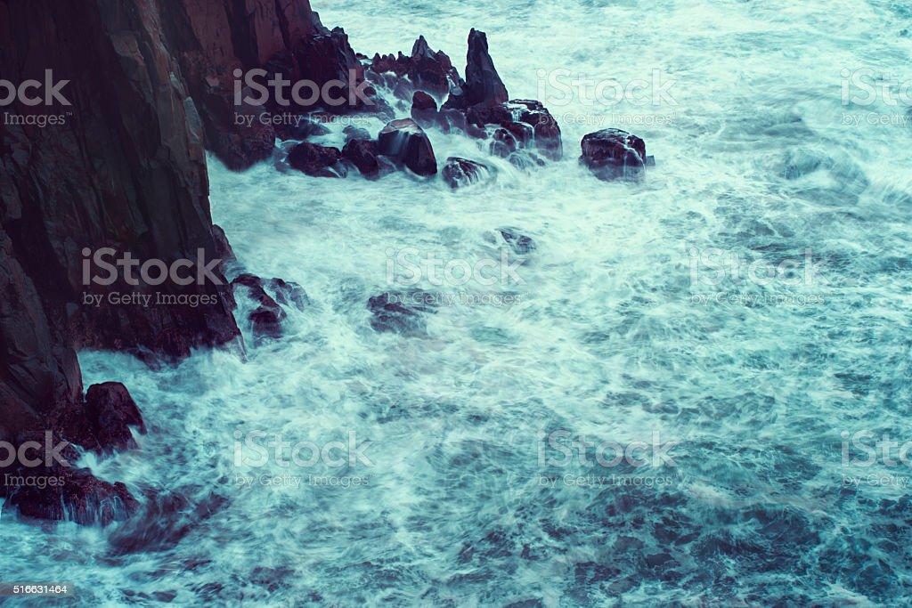 Crashing tide against the rocks stock photo