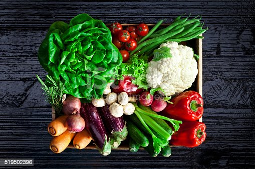 istock Crate filled with assortment of organic vegetables on black table 519502396