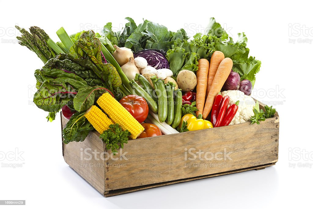 Crate filled with assortment of  organic vegetables on white backdrop stock photo