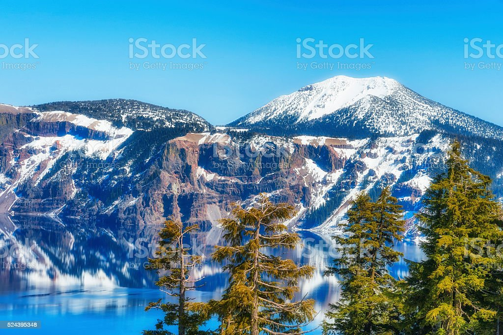 Crater Lake National Park Trees kissed by the afternoon sun along the southeast end of Crater Lake.  The Volcano's snowy rim reflects into the deep blue waters under blue skies Beauty In Nature Stock Photo