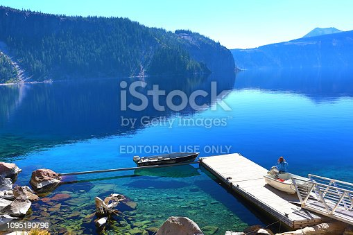 Bend, USA - September 3, 2018: Crater Lake boat dock with one person sitting by a boat next to the dock in a sunny day.