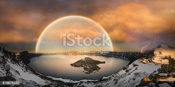 The panoramic view of Crater Lake with rainbow and lightning at sunset hour