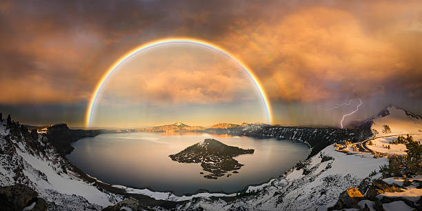 Crater lake with double rainbow and lightning bolt stock photo