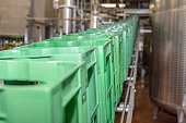 Many Crates in a row are transported to conveyor belt and moved to the filling line.