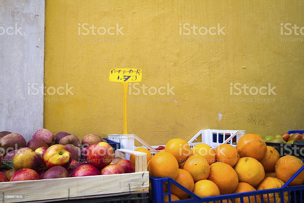 Crates of Apples and Oranges Against Vivid Umber Wall, Rome stock photo