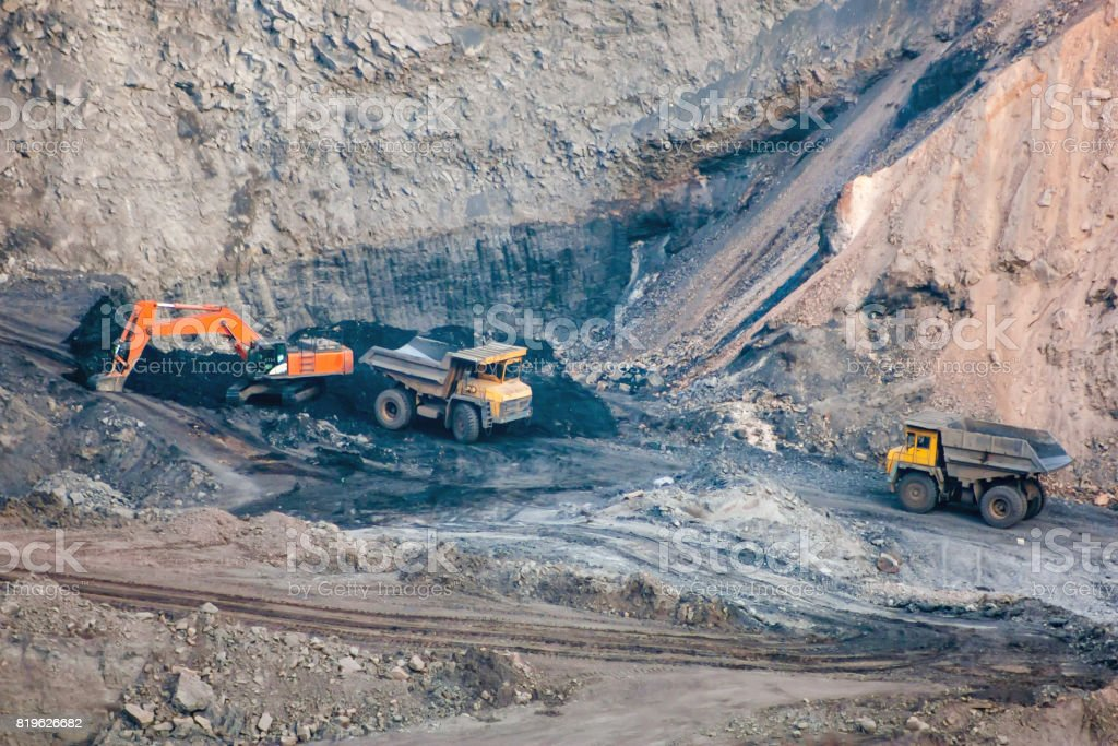 Crawler excavator and dump trucks are working in a quarry stock photo