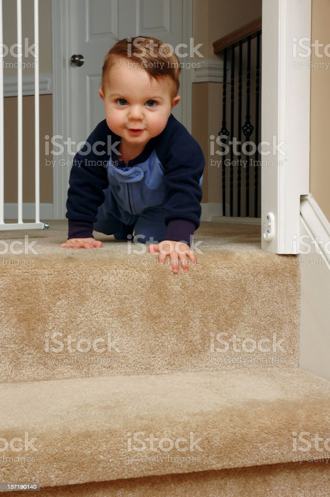 Crawling baby approaching stairs stock photo