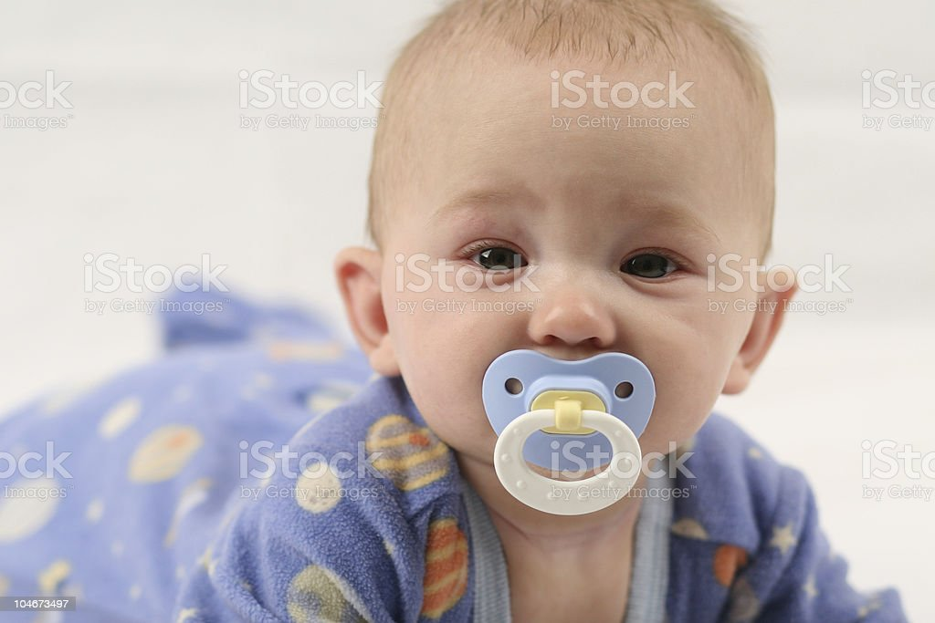 Crawling baby in blue with a blue pacifier stock photo