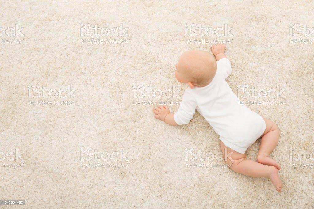 Crawling Baby on Carpet Background, Kid Top View, Newborn Child on Beige Blanket stock photo